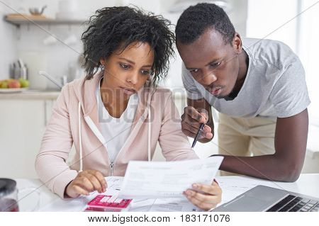 African man with pen in his hands pointing his wife at utility bill in front of him while doing paperwork trying to pay out all family debts sitting at kitchen table with calculator and laptop