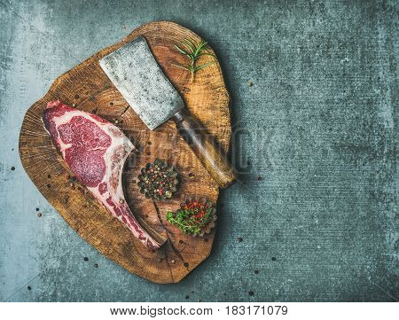 Dry aged raw beef rib eye steak with bone, butcher meat chopping knife and spices in bowls on rustic wooden board over grey concrete background, top view, copy space