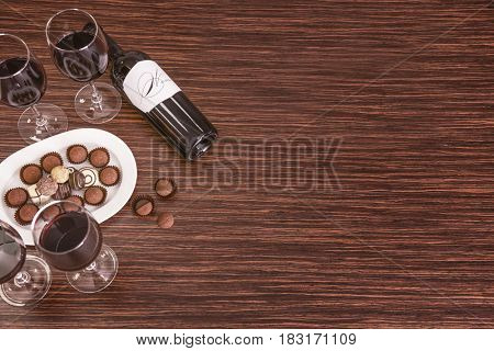 Glasses of wine and chocolates on wooden background