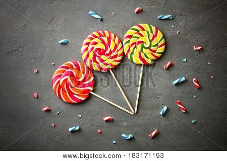 Composition with tasty lollipops on grey textured background