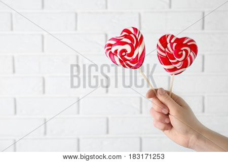 Female hand with tasty lollipops near brick wall