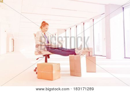 Full length of young businesswoman using laptop with feet up on cardboard box in new office
