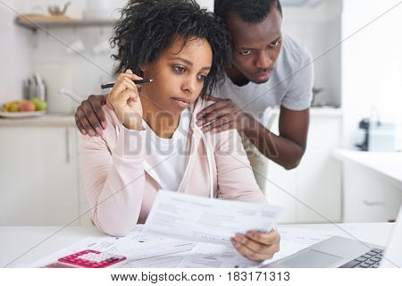 African american female analyzing unpaid bills with her supporting husband looking at laptop screen using online bank application. Young bankrupt couple have Financial problems. No money concept