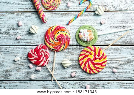 Composition with tasty colorful lollipops on wooden background