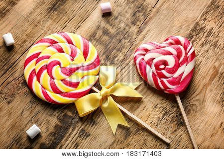 Tasty colorful lollipops on wooden background, closeup