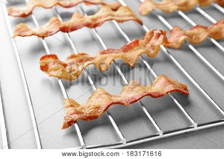 Grill with strips of fried bacon on table
