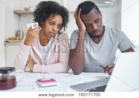 Young african american family sitting at kitchen table. feeling unhappy because financial problem and economic crisis trying to solve troubles reviewing their finances using online bank application
