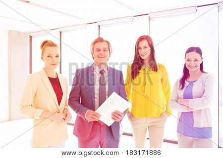 Portrait of mature businessman with female colleagues in new office