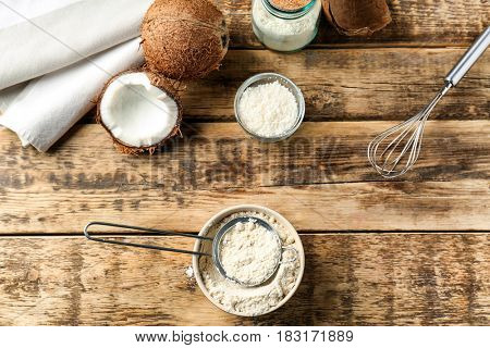 Bowl with coconut flour and sieve on wooden background