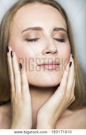 Close up portrait of young blonde beautiful girl with nude make up, with hands stroking her face with closed eyes on white background