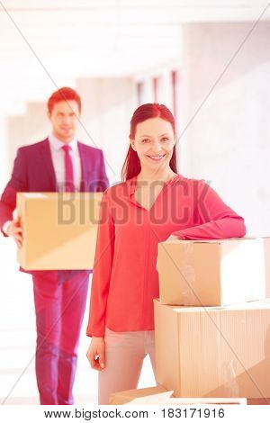 Portrait of confident businesswoman standing by stacked boxes with male colleague in background at office