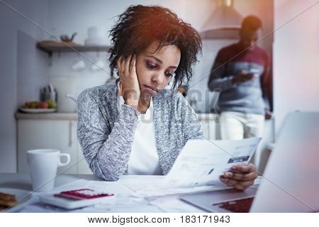 Stressed young African american woman doing paperwork at home having frustrated look while reading notification from bank failed to pay loan in time while husband checking account balance online