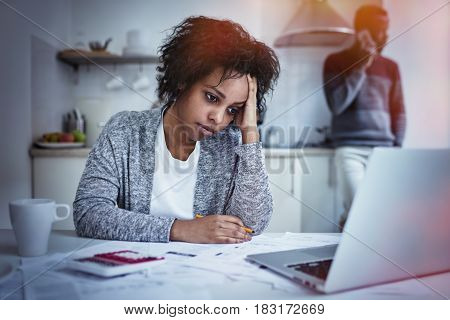 Stressed unhappy young African american female having headache while calculating family budget at kitchen table using calculator and laptop computer while husband making call to bank on background