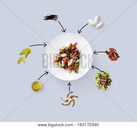 Cooking healthy food, seafood salad, isolated on blue. King prawn, shrimps, lettuce, avocado, mozzarella and other ingredients near plate with dish