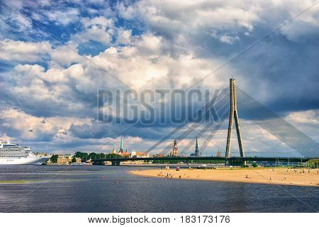 Sandy beach on the banks of the Daugava river on the background of cable-stayed bridge and the panorama of the city with spires and ship in port.