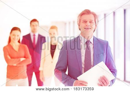 Portrait of confident businessman holding document with team in background at office