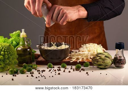 Chef's hands with a salt-mill spicing white cabbage placed in a dark bowl. Cooking concept