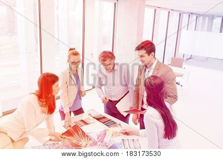 High angle view of design professionals having discussion at table in new office
