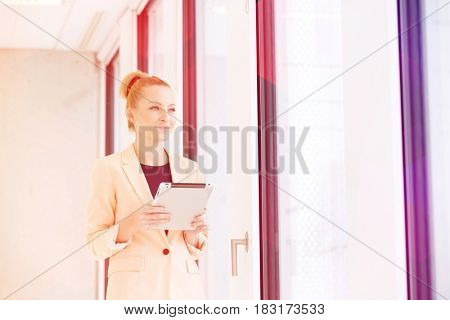 Young businesswoman holding digital tablet while looking away in office