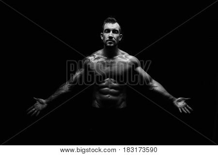 Strong athletic man. Handsome male fitness model showing naked torso, muscular body. Strong muscles and biceps. Studio shot, black and white. Bodybuilding concept
