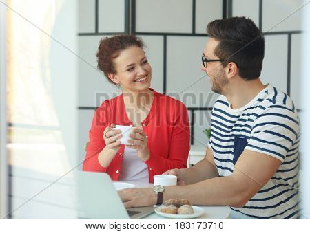 Happy young couple with laptop at home, view through window