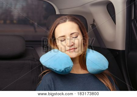 Young woman sleeping in car with pillow