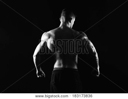 Unrecognizable man bodybuilder silhouette, strong back muscles, athletic trapezius. Black and white, studio shot on black background.
