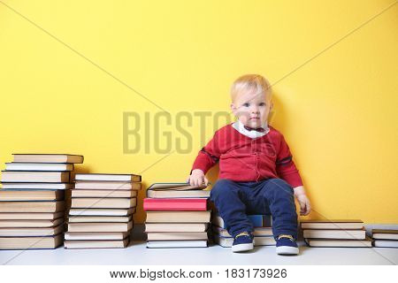 Cute little boy with plenty of books near color wall