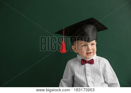 Cute little boy with magister hat and blackboard on background