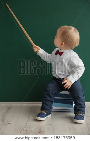 Cute little boy with pointer sitting on pile of books near blackboard