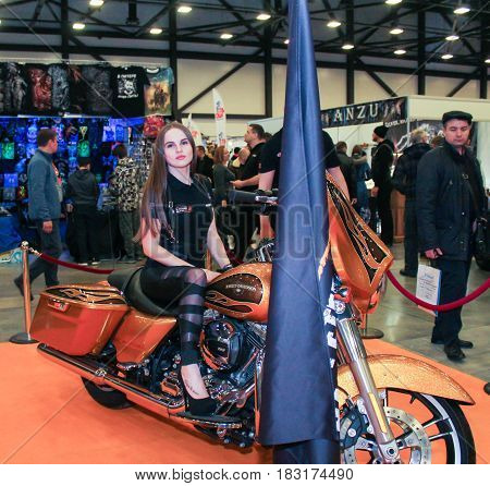 St. Petersburg Russia - 15 April, A girl is posing on a big motorcycle,15 April, 2017. International Motor Show IMIS-2017 in Expoforurum. Models on motorcycles presented at the motor show.