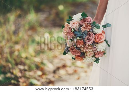 Wedding bouquet from rose flowers in unrecognizable bride's hand. Bridal floral decoration detail outdoors in summer park, copy space