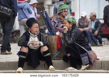 Sa Pa, Vietnam - March 15, 2017: Hmong women in a traditional costume trying to sell her goods on the market. Hmong people is a minority ethnic group living in Sapa.