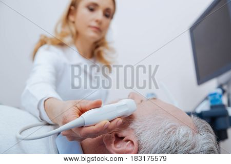Caring about aged generation. Attractive concentrated qualified practitioner working in the clinic while providing ultrasound brain examination and using medical equipment