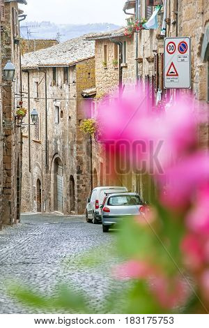 Little street with stone houses, flowers and cars in Orvieto, Italy, Toscana