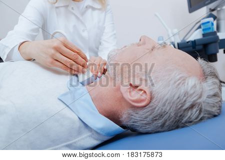 Prevention checkup of thyroid gland. Senior motionless bearded patient lying on the medical couch and getting ultrasound thyroid examination while doctor using ultrasound linear transducer