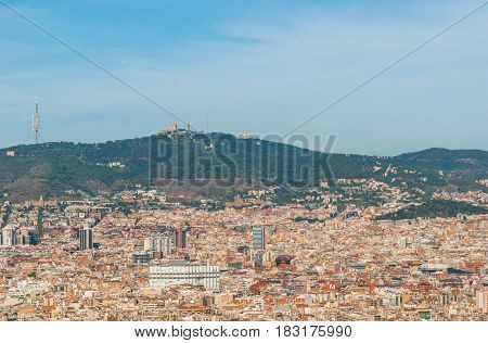Barcelona cityscape view from high a level, cable car as it passes over tree tops providing views of the city.