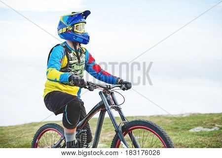 A young guy sits on a mountain bike atop a mountain, when below the mountains low clouds and fog.