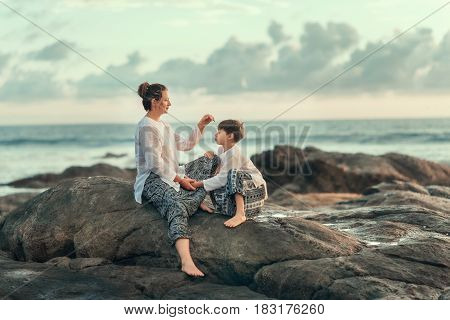 Summer cloudy day by the sea on large stones sit mother and son