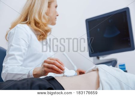 Digital ultrasound machine in use. Smart qualified female physician working in the clinic while providing ultrasonic scanning of stomach and using ultrasound linear transducer and ultrasound machine