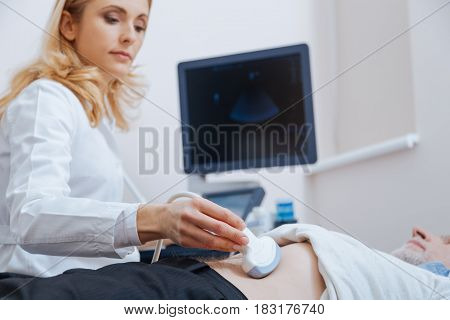 Searching for echo sound waves. Serious attractive female physician working in the clinic while providing ultrasonic monitoring of stomach and using ultrasound machine