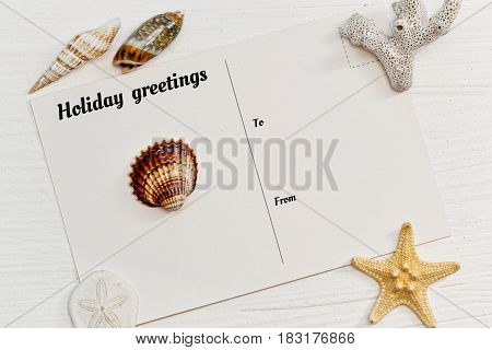 Blank postcard with vacations tagline and some sea shells on the rude wooden surface