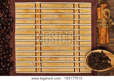 Bamboo square mat with wooden spoon with clove seed cinnamon sticks and roasted coffee beans in top view