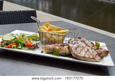 Plate of grilled meats with fries and salad on a table along the Moselle