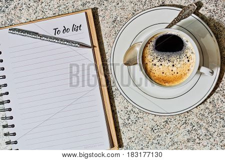 Cup with espresso coffee and opened planning notebook with to do list on modern office table