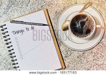 Calendar notebook with to do list on the table in cafe and a cup with espresso