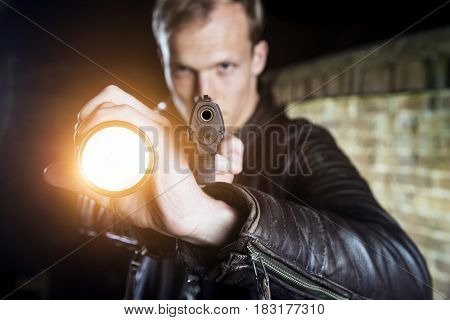 Plain clothes law enforcement officer holding a flash light, and pointing his gun at the camera during an arrest at night
