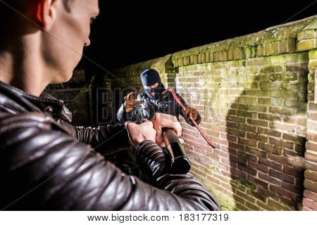 Policeman Aiming Pistol Towards Scared Cracksman At Night