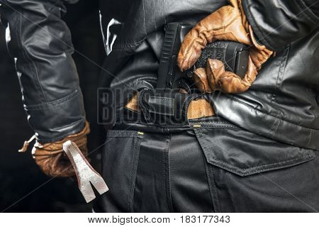 Criminal, wearing a black leather jacked, black pants and leather gloves, holding a crow bar, reaching for a concealed gun, tucked in the back of his trousers.