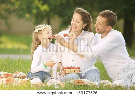 pregnant mother, happy father and daughter on a picnic in the Park on Sunday